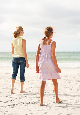 Buy stock photo Rear view of a mother and daughter taking a strolling on the beach