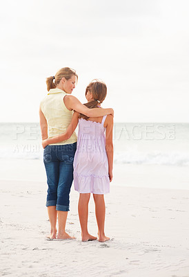 Buy stock photo Beach vacation - Rear view of a mother and daughter standing together at the sea shore