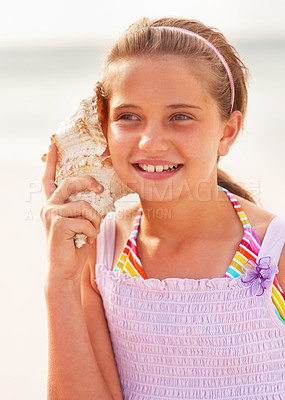 Buy stock photo Happy teenaged girl hearing a conch shell at the beach