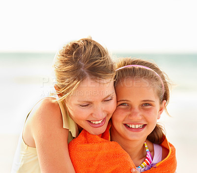 Buy stock photo Cute young girl being hugged by her mother while on their beach vacation