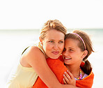 Caring mother embracing her daughter while at the sea shore