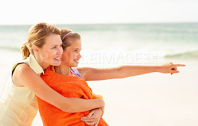 Buy stock photo Cute young girl being hugged by her mother pointing away while on their beach vacation