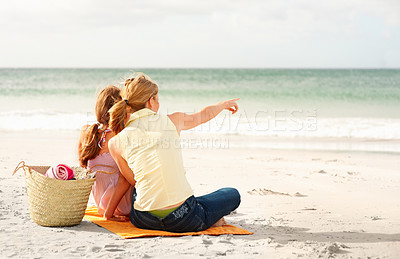 Buy stock photo Rear view of a mother and teenaged daughter sitting on the beach, woman pointing towards the sea