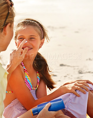 Buy stock photo Cut image of mother applying sun cream of daughter's nose while at the beach