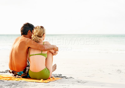 Buy stock photo Rear view of a romantic couple sitting on the sea shore facing the ocean