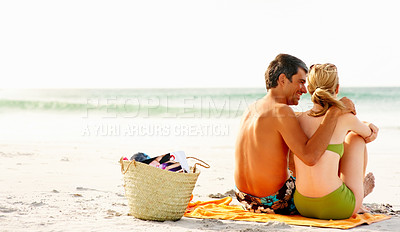 Buy stock photo Beach picnic - Rear view of a happy couple sitting at the sea shore