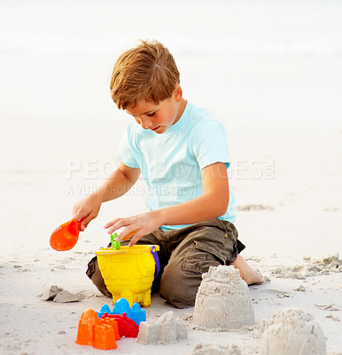 Buy stock photo Adorable young boy playing at the beach, making sand castle