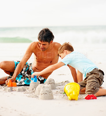 Buy stock photo Happy father and son making sand castles, playing at the sea shore