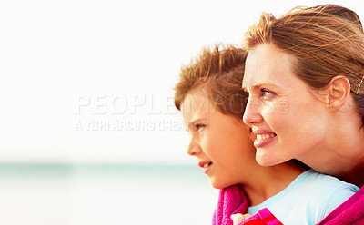 Buy stock photo Mother hugging her cute son while at the sea shore, looking at copyspace