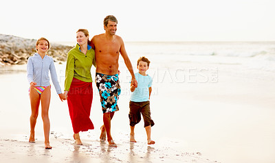 Buy stock photo Beach vacation - Family of four taking a strolling on the sea shore