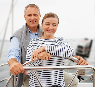 Buy stock photo Portrait of a happy retired steering a boat on their voyage