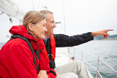 Buy stock photo Happy retired couple enjoying a sea voyage vacation, man pointing away