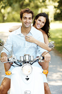 Buy stock photo Cropped shot of a young couple riding their scooter in the park