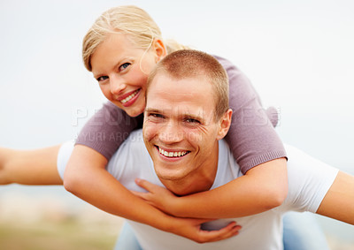 Buy stock photo Handsome young male piggybacking his girlfriend, outdoors