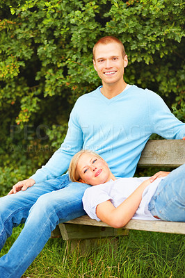 Buy stock photo Cute young couple relaxing on a bench at the park, female lying on man's lap