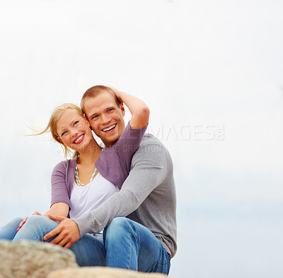Buy stock photo Happy romantic young couple relaxing on the rocks by the beach