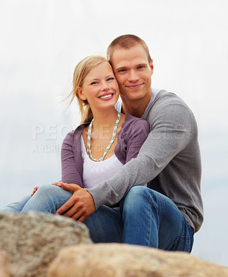Buy stock photo Portrait of a cute young couple relaxing on the rocks, beach view