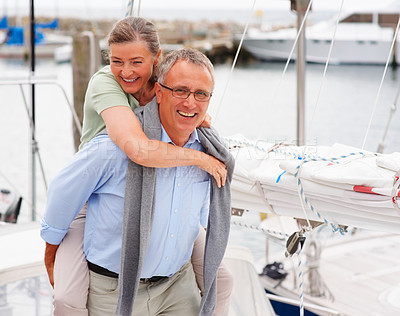 Buy stock photo Happy senior couple in a playful mood while on a sailboat