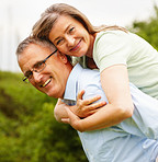 Cute senior woman being piggybacked by her husband at the garden