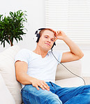 Smart young man listening to music while relaxing at home