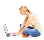 Cute young female using a laptop while seated on the floor, white background