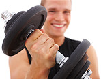 Young guy exercising with dumbbell, focus on the dumbbell