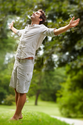 Buy stock photo Full length shot of a young man standing with his arms outstretched in the park