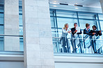 Group of colleagues discussing business by a glass railing