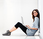 Young lady sitting on floor working on a laptop smiling