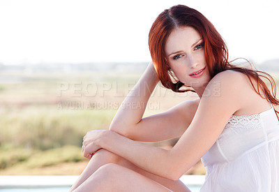 Buy stock photo A young redheaded woman sitting outside