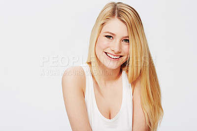 Buy stock photo A pretty young blonde sitting against a white background and looking at you