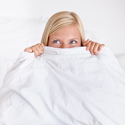 Buy stock photo A cute young woman peeking out from the top of her duvet