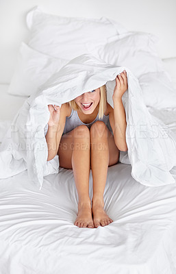 Buy stock photo A pretty young blond woman peeking from under the covers in her bedroom happily