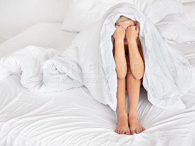 Buy stock photo A depressed young woman looking out from under her blanket sadly