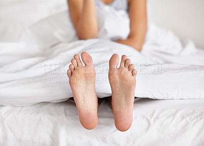 Buy stock photo Shot of a pair of woman's feet poking out from under the sheets of a bed