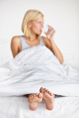 Buy stock photo Shot of a young woman drinking water while lying on a bed with her feet poking out of the covers