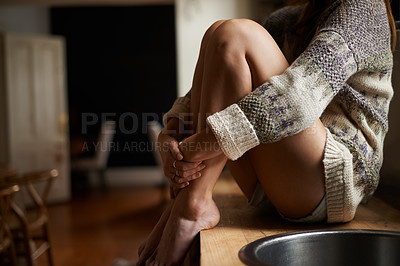 Buy stock photo Neck down shot of a young woman sitting on the counter in a rustic kitchen bathed in window light
