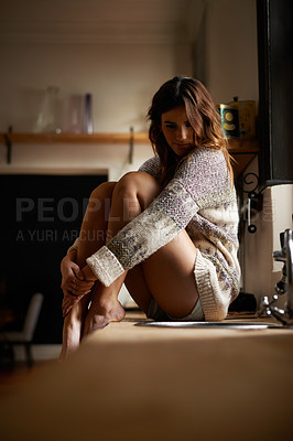Buy stock photo Portrait of a young woman sitting alone on the counter in a kitchen