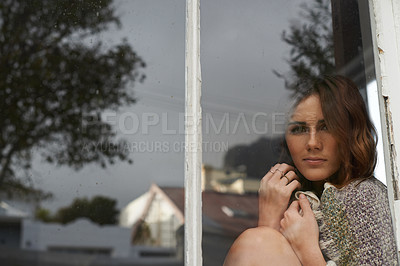 Buy stock photo Portrait of an attractive young brunette woman looking through a rustic window