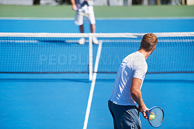 Buy stock photo Rearview shot of a man about to serve a ball during  a tennis match