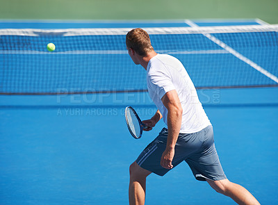 Buy stock photo Rearview shot of a man hitting a ball on a tennis court