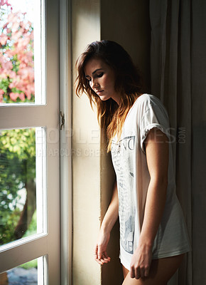 Buy stock photo Cropped view of a young woman standing at the window at home