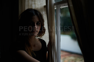 Buy stock photo Cropped portrait of a young woman at the window of her home