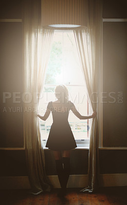 Buy stock photo Full length rear view of a young woman looking out the window