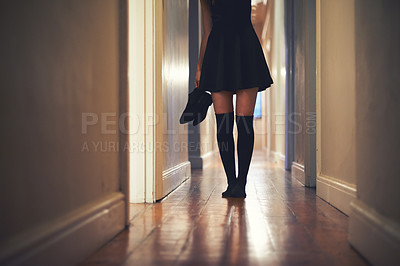 Buy stock photo Cropped image of a young woman walking down the hallway in her house