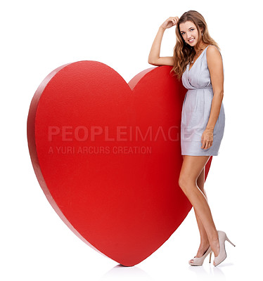 Buy stock photo Portrait of an attractive young woman standing behind a giant heart-shaped prop