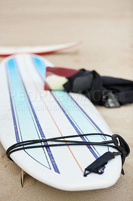 Buy stock photo A surfboard and wetsuit lying on the sand at the beach