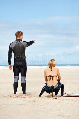 Buy stock photo Two surfers sitting on the beach while one points towards the ocean