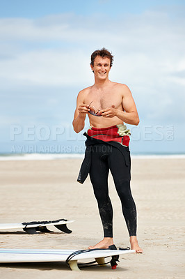 Buy stock photo Smiling young surfer standing on the beach holding his shades