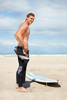 Buy stock photo A young surfer standing on the beach with his surfboard